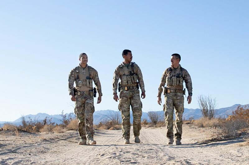 Three Border Patrol Search, Trauma and Rescue Unit agents walking through the desert.