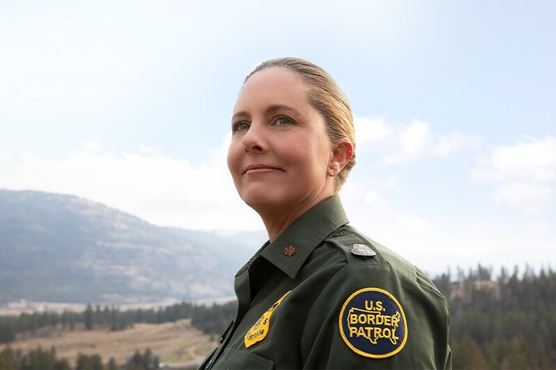 Profile Portrait of Female Border Patrol agent who is in front of a wooded background