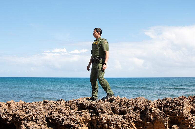 Border Patrol agent standing on a cliff near water.