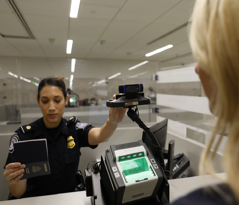Female CBP Officer using facial recognition technology on a traveler