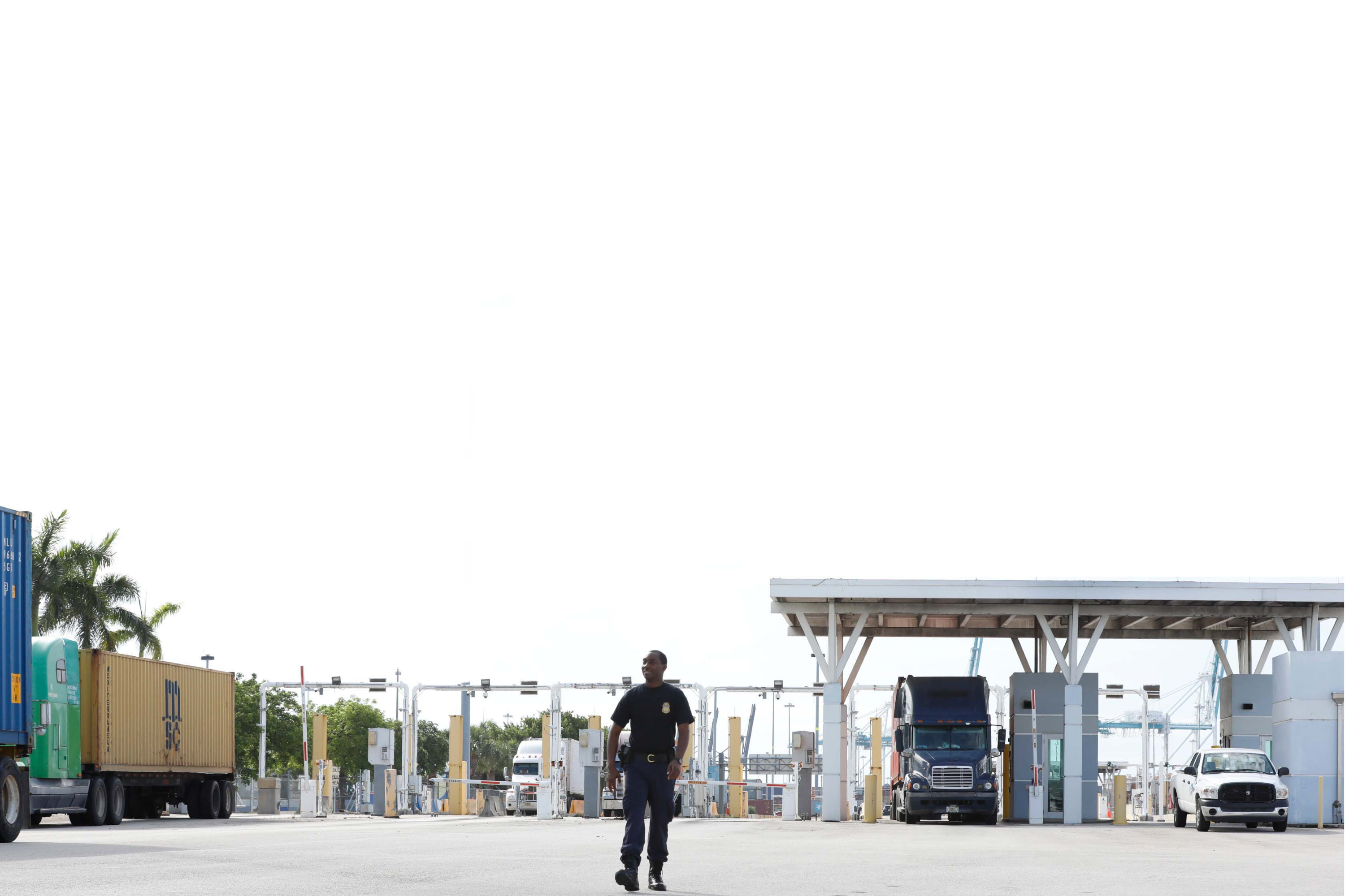 Male CBP Officer walking in front of cargo containers