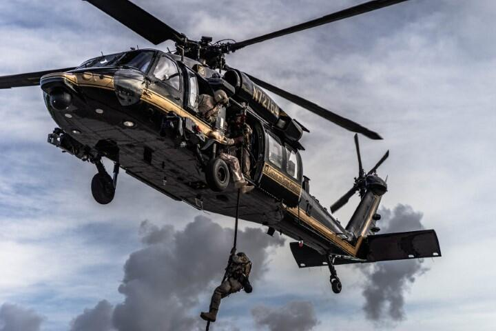 An Air and Marine Operations agent rappels from a UH-60 Black Hawk helicopter.