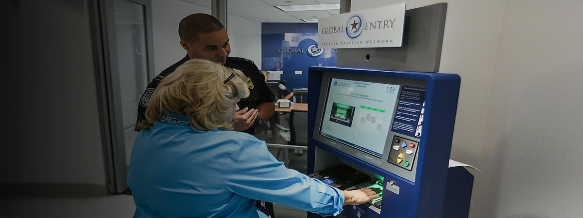 CBP Officer showing a female how to use the global entry kiosk