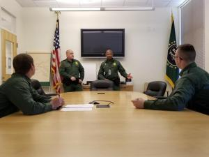 Border Patrol Academy trainees Thomas Gursky (far left) and Justin Franklin (far right) listen as Patrol Agent in Charge Jarom Linde and Supervisory Border Patrol Agent Shelton McKenzie brief them on what they'll be doing at the Orlando, Florida, Border Patrol station. Photo by Supervisory Border Patrol Agent Richard Torres