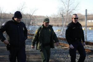 CBP officers in the blue uniforms work with a Border Patrol agent along the U.S.-Canada border. Photo by Sid Lagos