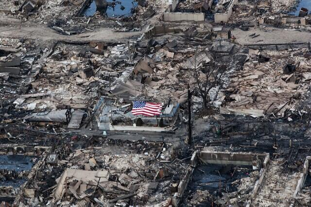 Photo of a flag amongst burnt homes