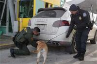 A Border Patrol agent and a CBP officer train a CBP canine to detect contraband in or around a vehicle