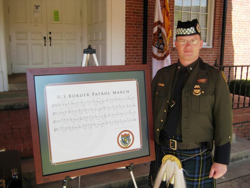 Assistant Chief Clifford Gill, then Commander of the USBP P&D, accepts a framed copy of the Border Patrol March, a gift of Gordon, James and Colin Bell of the Balmoral School of Piping and Drumming. It is currently on display at CBP Headquarters in the Office of Border Patrol. Photo April 2008.