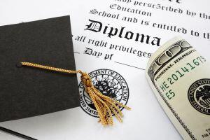 Graduation cap and money sitting on a diploma
