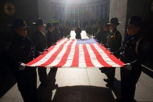 An outstretched flag is held by honor guards from both Border Patrol and the Office of Field Operations prior to a ceremony at the Ronald Reagan building.  Photographer: James Tourtellotte