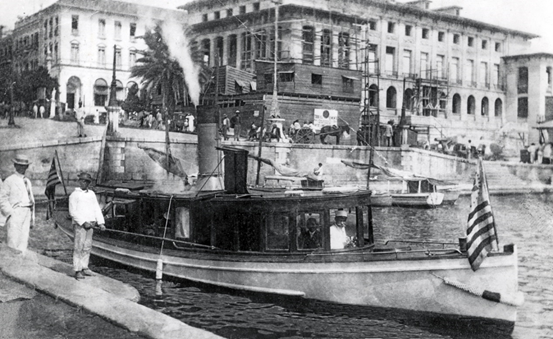 1905 - Customs cutter leaves the dock at the U.S. Custom House in San Juan, Puerto Rico. In the background is the U.S. Post Office then under construction.