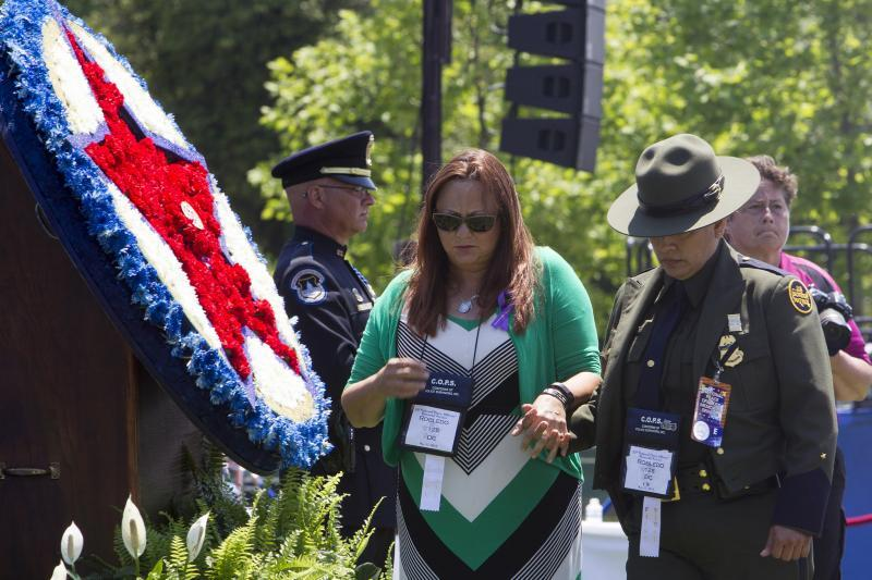 Toya Daniels, mother of fallen U.S. Border Patrol Agent Tyler R. Robledo, is escorted away from the memorial wreath by a U.S. Border Patrol agent May 15 during the 34th Annual National Peace Officers' Memorial Service in Washington, D.C. Photo credit: Donna Burton