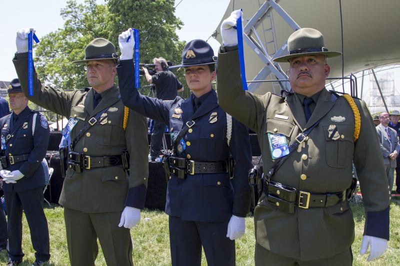 Two U.S. Border Patrol agents and a CBP officer hold up blue ribbons signifying solidarity near the end of the 34th Annual National Peace Officers' Memorial Service on the West Front of the U.S. Capitol in Washington, D.C. The ribbons honor the law enforcement officers who died in the line of duty, as well as the men and women who serve and protect communities every day. Photo credit: Donna Burton