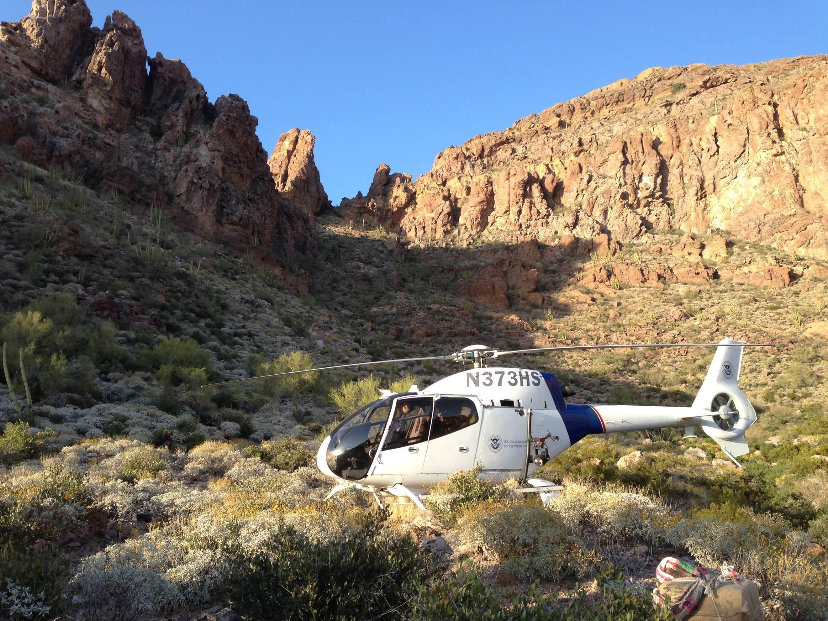 An Air and Marine Operations EC120 crew lands in the desert to retrieve bundles of marijuana near Yuma, Arizona.