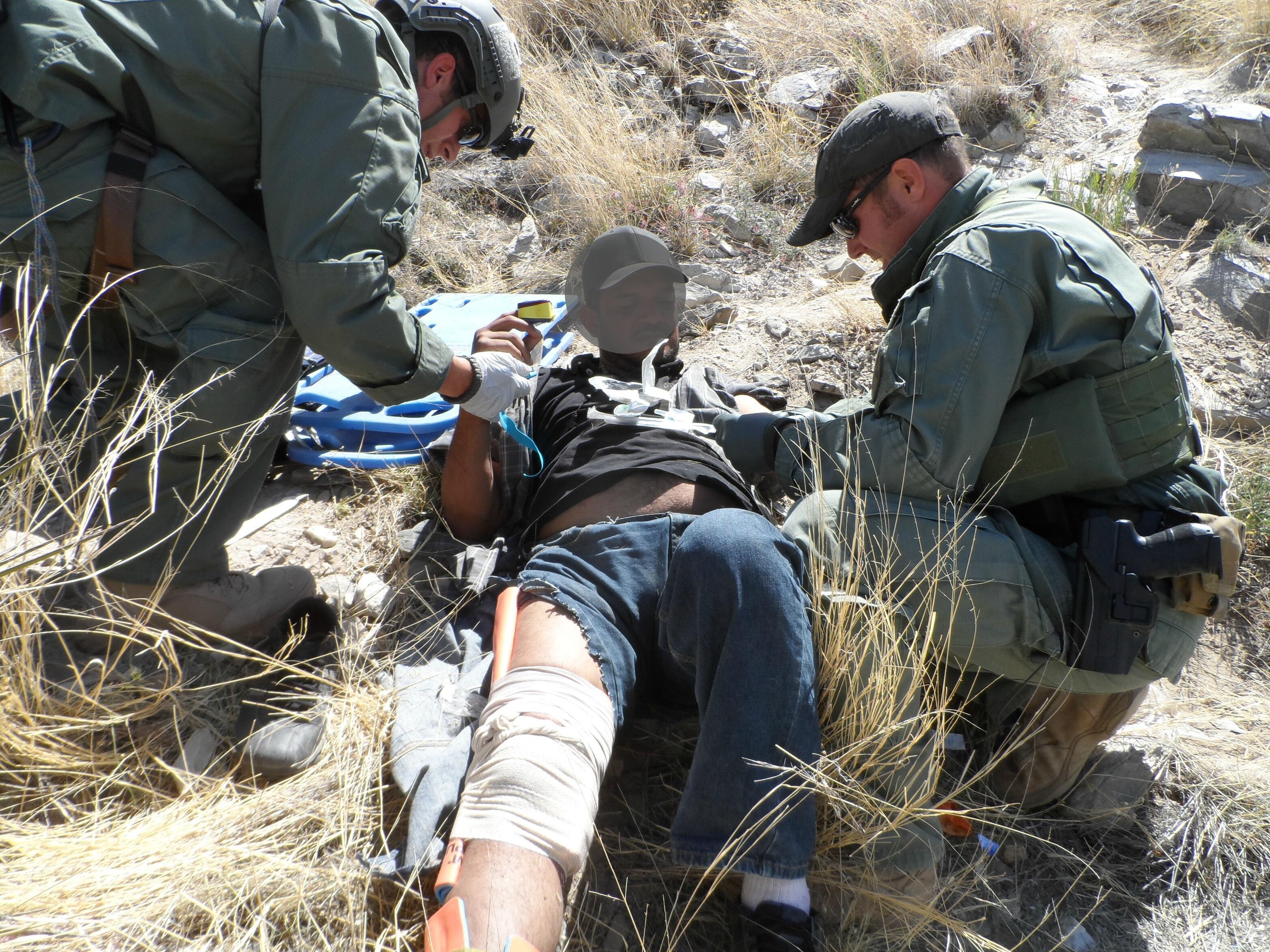 Miembros del Equipo de Búsqueda, Trauma y Rescate de la Patrulla Fronteriza (BORSTAR) rinden primeros auxilios a un migrante lesionado.