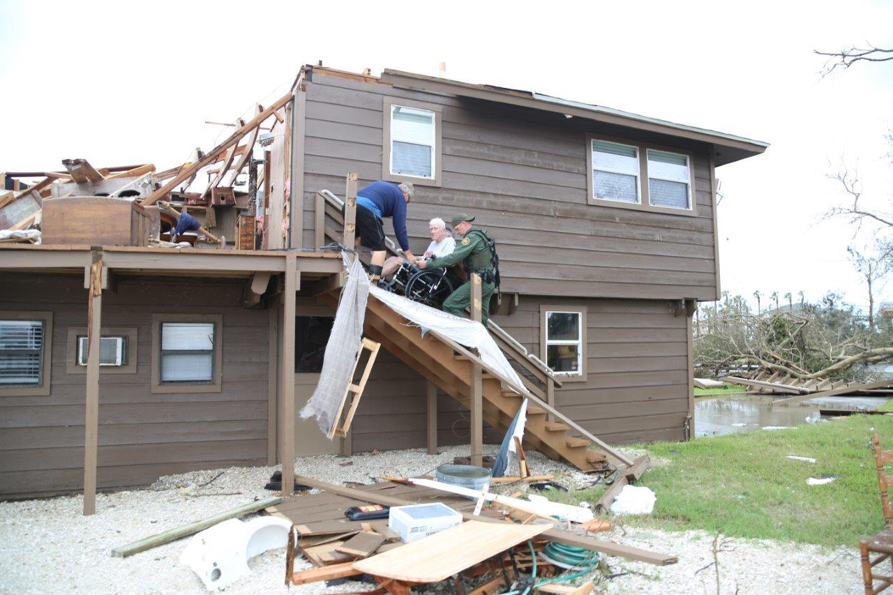 Rio Grande Valley Sector Border Patrol Special Operations Agents assist a disaster survivor trapped on the second floor of his home in Rockport, Texas August 26, 2017. <em>Photo courtesy of U.S. Customs and Border Protection.</em>
