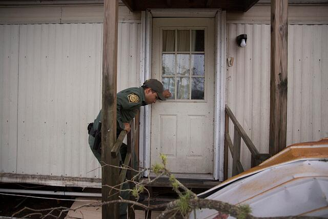 A U.S Border Patrol agent knocks on the door of a mobile home as he and his cohorts conduct search and rescue operations in the wake of Hurricane Harvey near Lockport, Texas. (August 27, 2017) U.S. Customs and Border Protection Photo: Glenn Fawcett