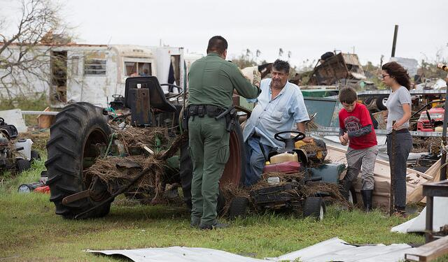 U.S Border Patrol agent Mario Fuentes talks with a family after Hurricane Harvey near Rockport, Texas. (August 27, 2017) U.S. Customs and Border Protection Photo: Glenn Fawcett