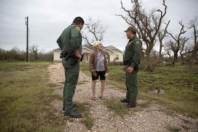 U.S Border Patrol agents Mario Fuentes, left, and Marc Gonzales talk with a woman who rode out Hurricane Harvey in her home near Rockport, Texas. (August 27, 2017) U.S. Customs and Border Protection Photo: Glenn Fawcett