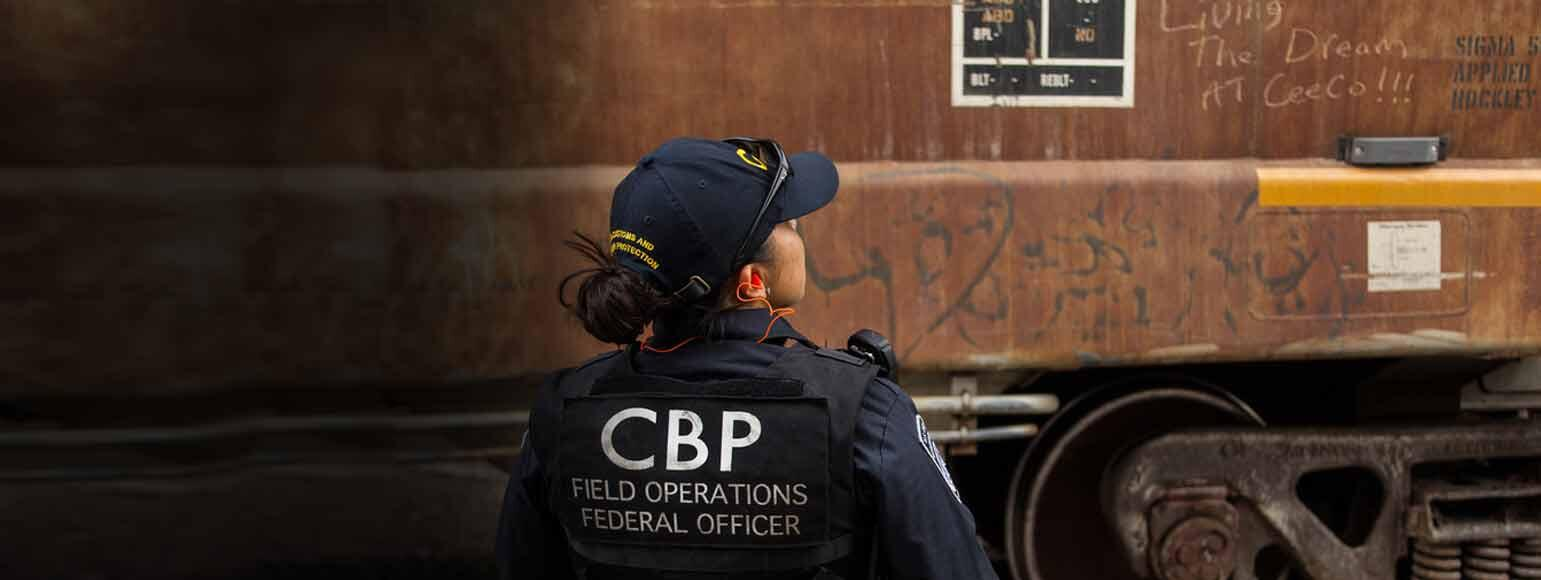 CBP Officer inspects rail car for hidden fugitives.