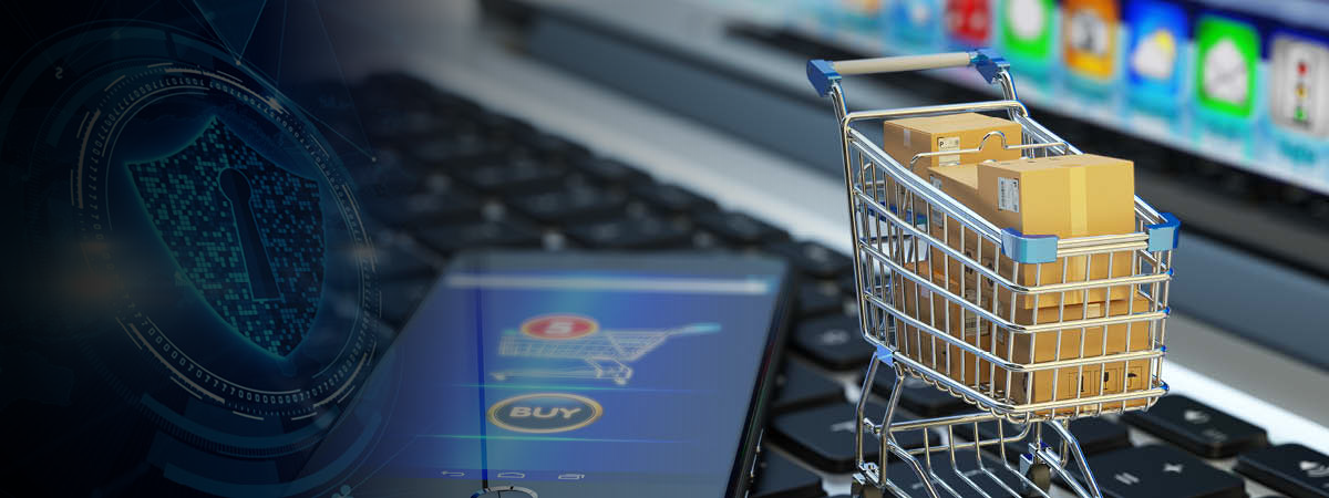 Laptop with a two items on top; (1) shopping cart with boxes and (2) cell phone on buy screen