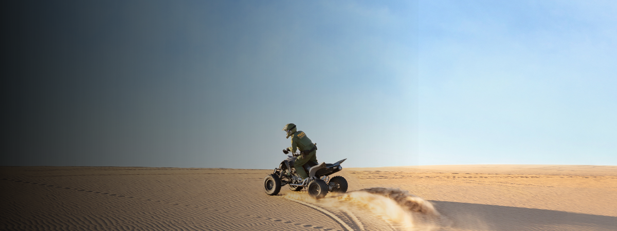 Border Patrol agent riding ATV in the desert
