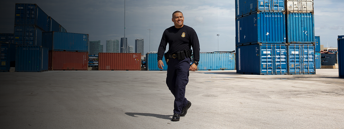 Male CBP Officer walking in front of cargo at a port of entry