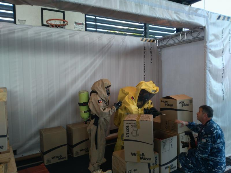 Two individuals in WMD protective clothing conducting an inspection during an exercise