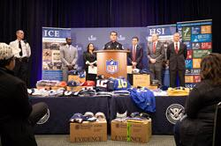 CBP Deputy Commissioner Robert Perez in Atlanta unveils a cache of seized phony Super Bowl paraphernalia.
