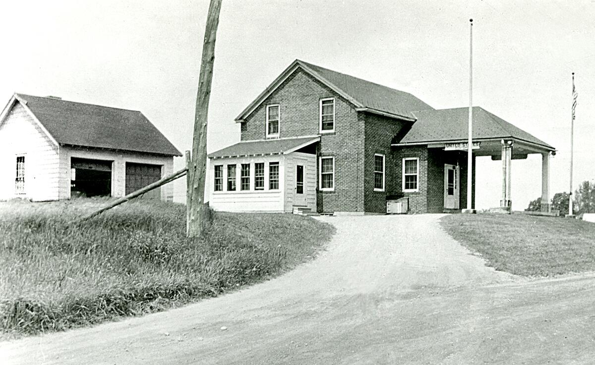 1940's photograph of the U.S. border inspection station at Morses Line, Vt. The border station was built in 1935 on the west side of Morses Line Road (State Route 235.) A small office for the Customs and Immigration inspectors stationed at the port is accessed from door opening off the canopied driveway. Residential quarters for the officers and their families consisted of living rooms and kitchens at the rear of the first floor, which were accessed by enclosed private entrances on both sides of the building; bedrooms and bathrooms were located on the second floor An identical size border inspection station was constructed in Alburgh Springs, Vt. in 1937, and it too is still in operation today.