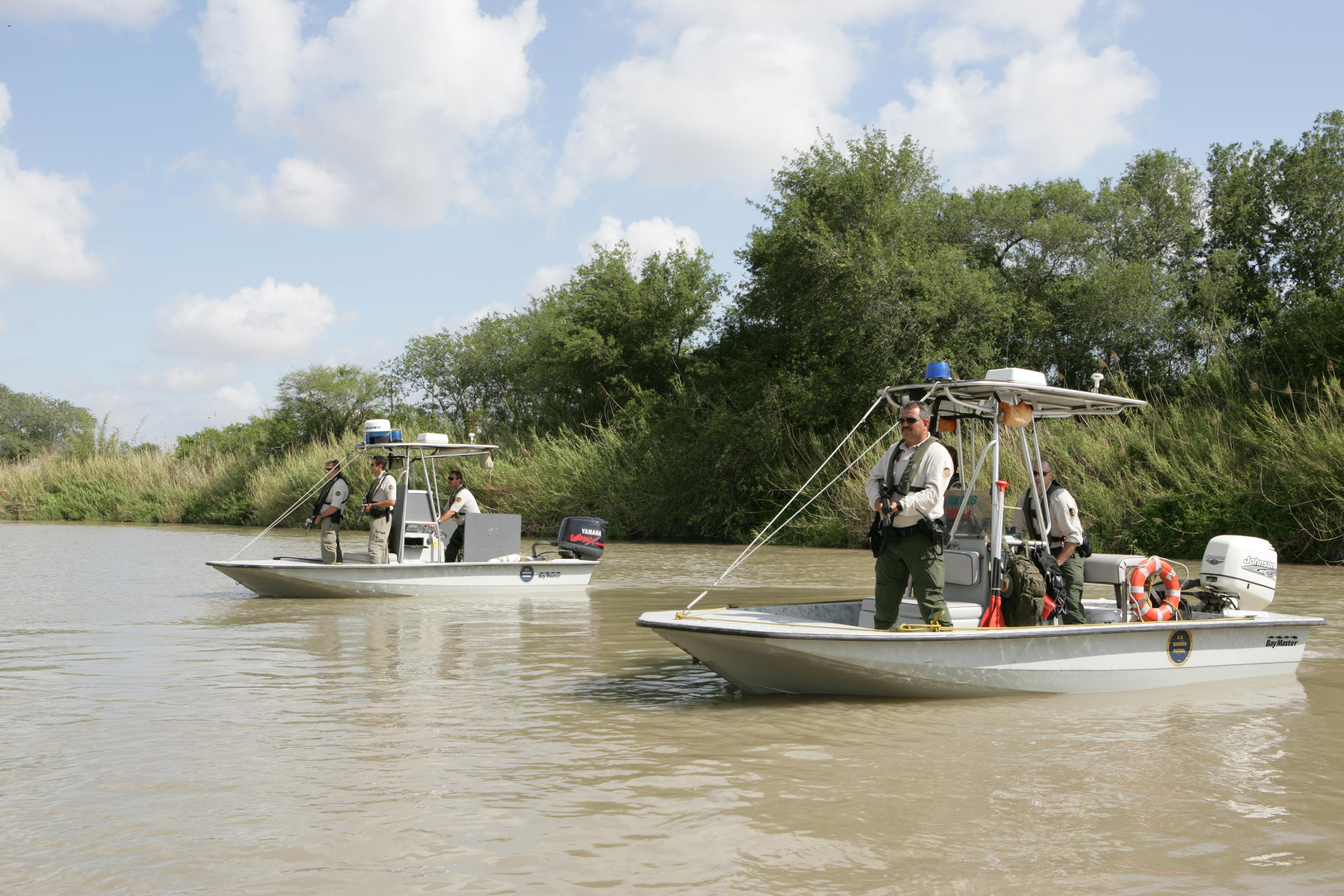 U.S. Border Patrol Marine units face toward Mexico to provide cover for other agents on the U.S. side of the river conducting an investigation.