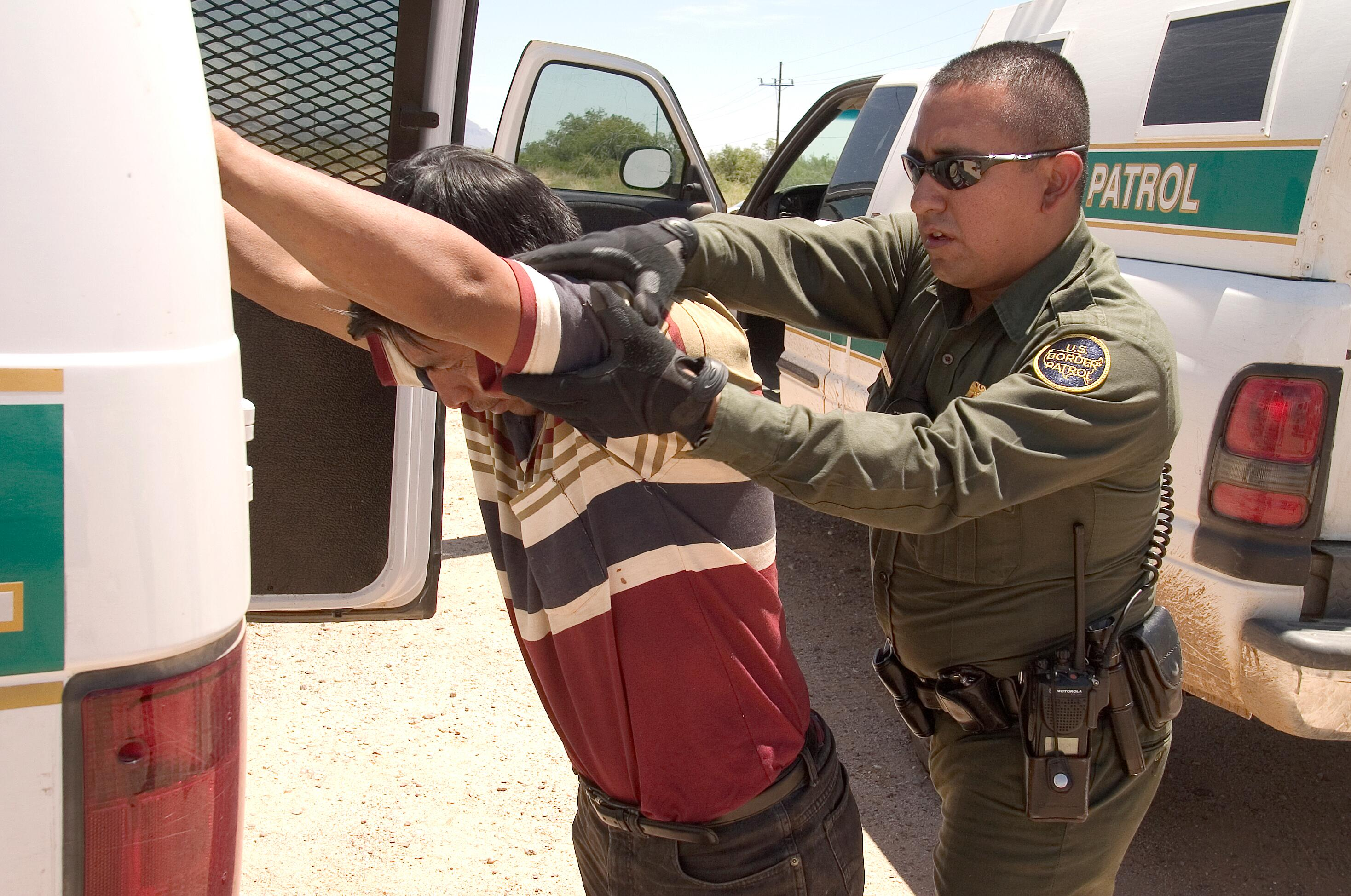 U.S. Border Patrol agent does a pat down of a Mexican being returned to Mexico.