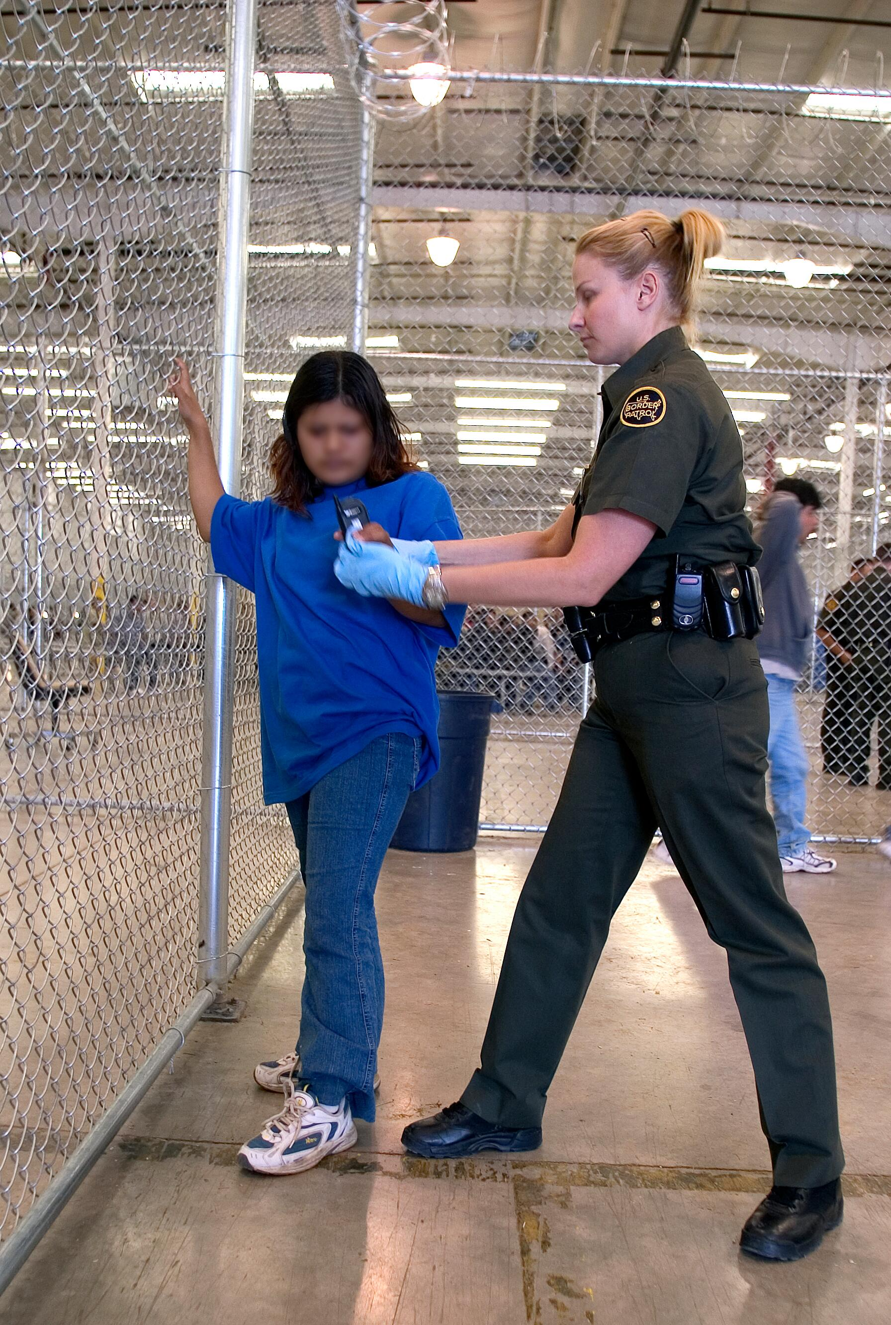 U.S. Border Patrol agent conducts a pat down of a female Mexican being placed in a holding facility.