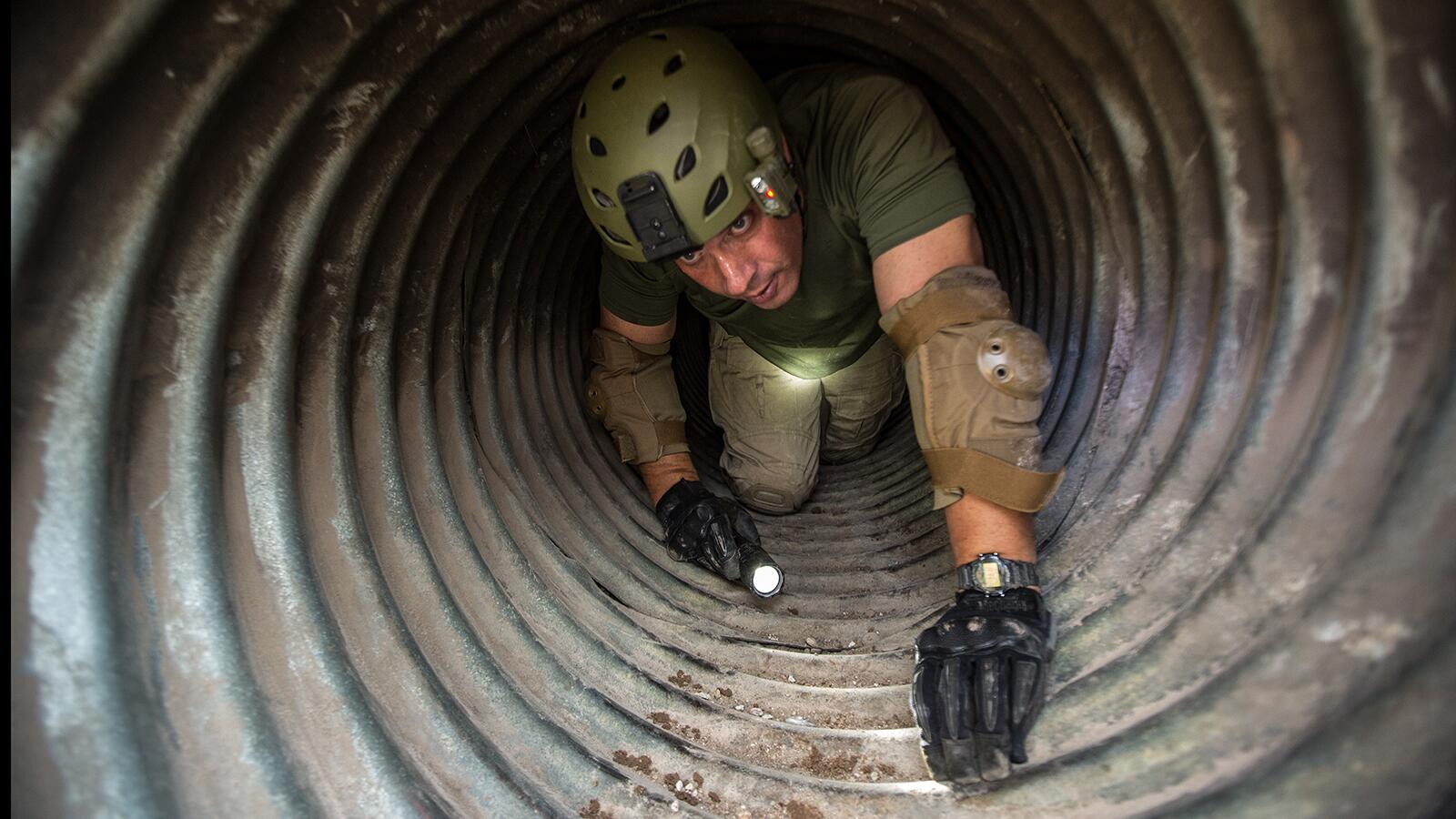 Supervisory Border Patrol Agent Kevin Hecht crawls through the drainage pipe looking for evidence left behind by the illegal tunnelers.