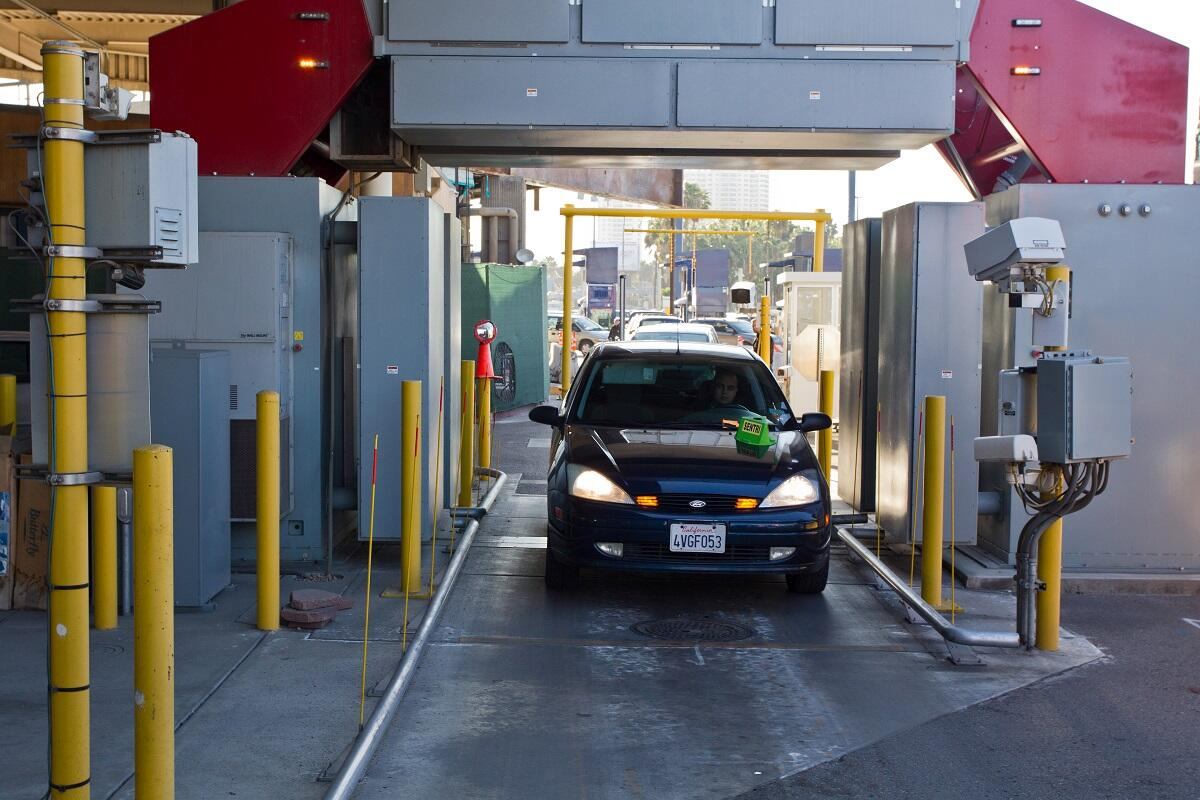 A car passes through an inspection booth and hi-tech scanners at the San Ysidro, Calif. port of entry. (photo by Josh Denmark)