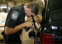 CBP officer inspects fuel tank of a vehicle