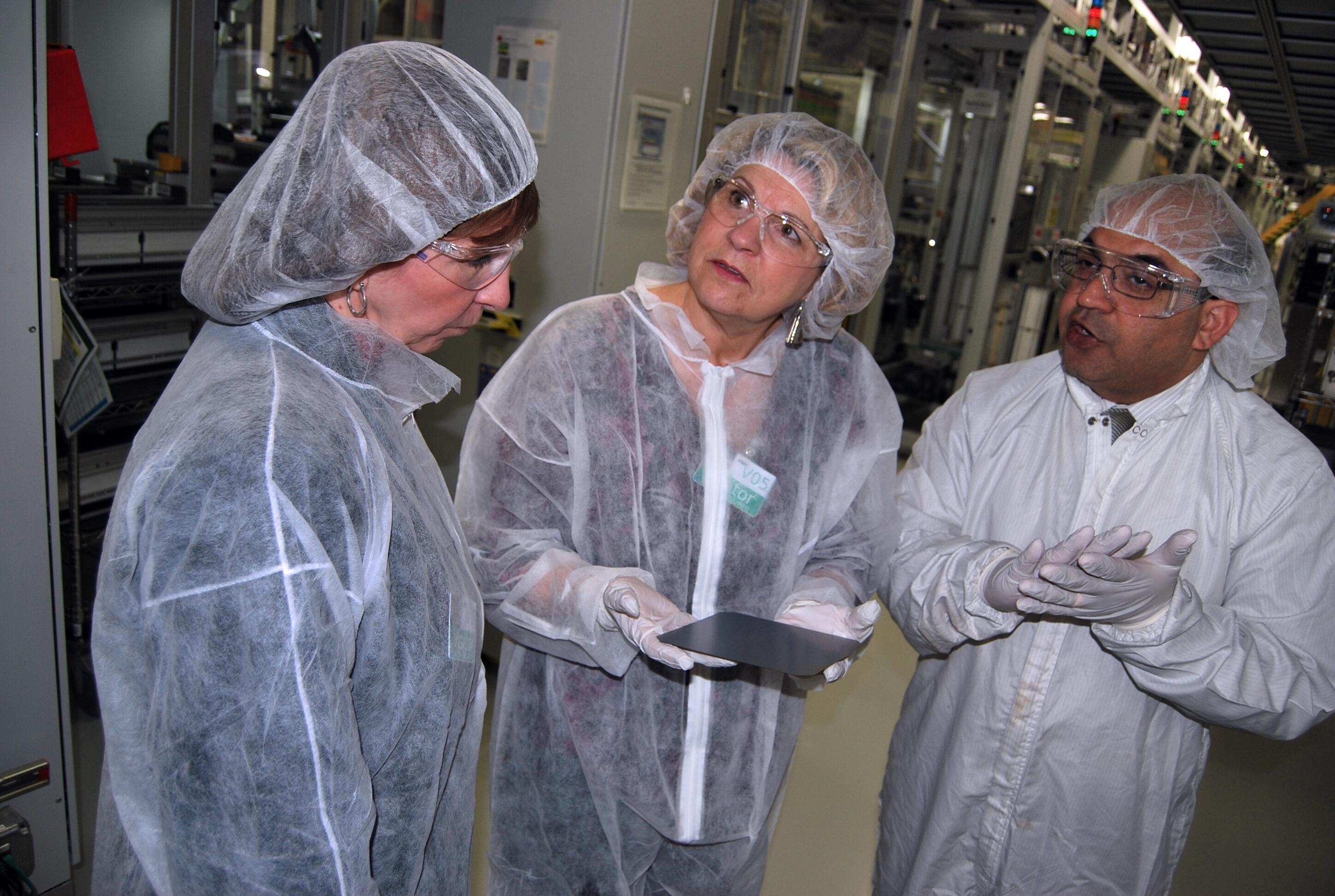 SolarWorld President Mukesh Dulani, right, describes the technology used to produce the fragile solar cell held by CBP Senior Import Specialist Katie Schultz, center, while CBP Import Specialist Kristy Huckins listens. Photo by Ed Colford