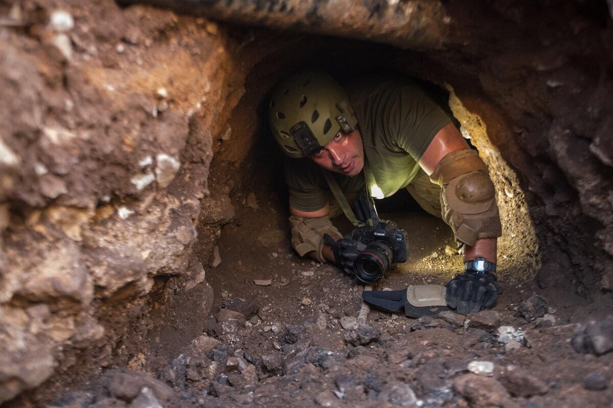 A Border Patrol agent inspects a man-made tunnel near Nogales, Ariz. Such tunnels are used to transport drugs under the U.S. border.<em> (photo by Josh Denmark)</em>
