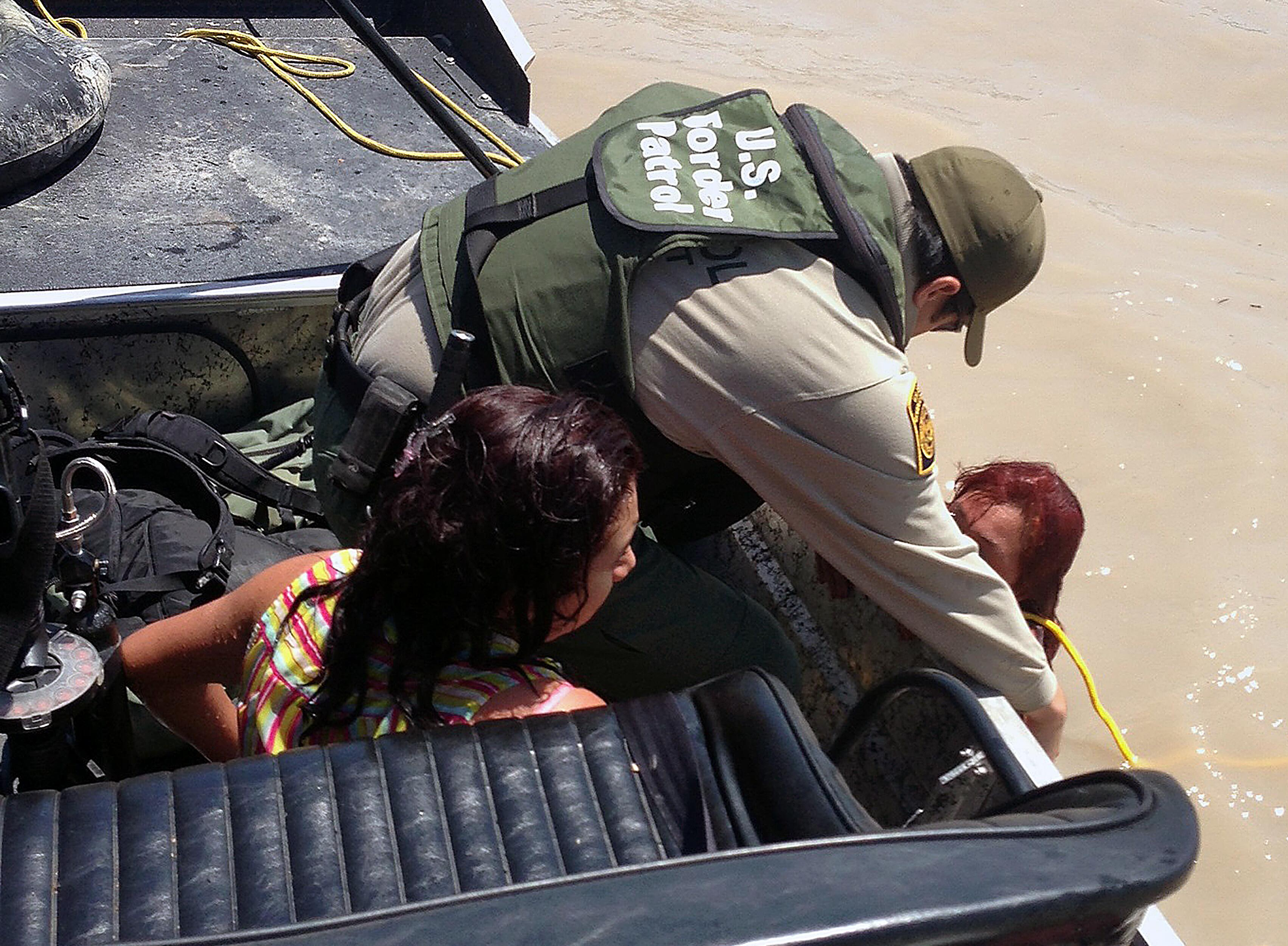 Border Patrol agents from Eagle Pass, Texas rescue a woman and her daughter from the Rio Grande River. The El Salvador citizens were struggling to stay afloat when spotted by agents, who deployed flotation devices and pulled them from the water. <em>(Photo by Border Patrol Agent Carl Nagy)</em>