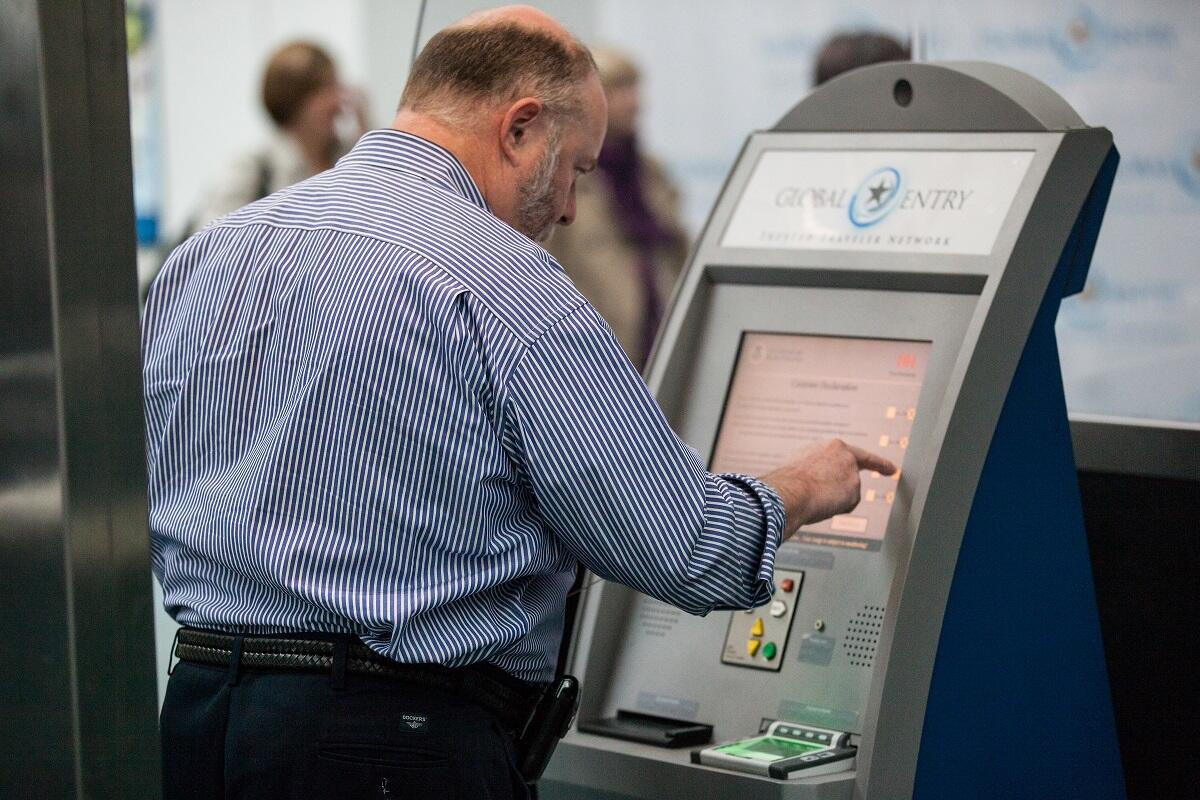 An arriving passenger at Newark [N.J.] Liberty International Airport uses a Global Entry kiosk to enter the U.S.<em> (photo by Josh Denmark</em>)