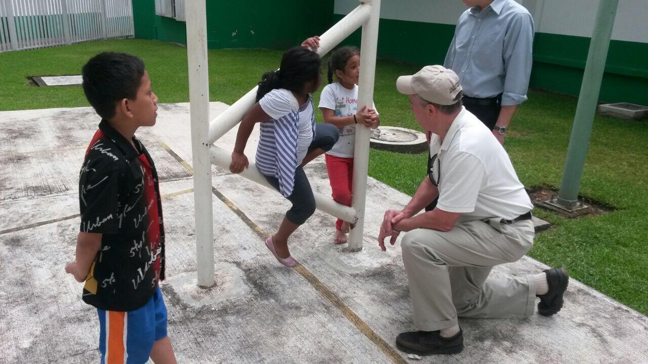 Commissioner speaking with migrant children