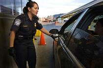 A CBP Officer inspects a vehicle and passengers at a land border port of entry