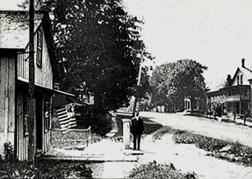 View of the U.S. Custom House (at left) on Main Street in Franklin, Vermont, with Customs flag flying and Deputy Collector & Inspector Adolphus Dewing Whitney standing on the town scale. Mr. Whitney and his family lived in the house standing next to the general store on the right. Vintage postcard photo franked in 1909.