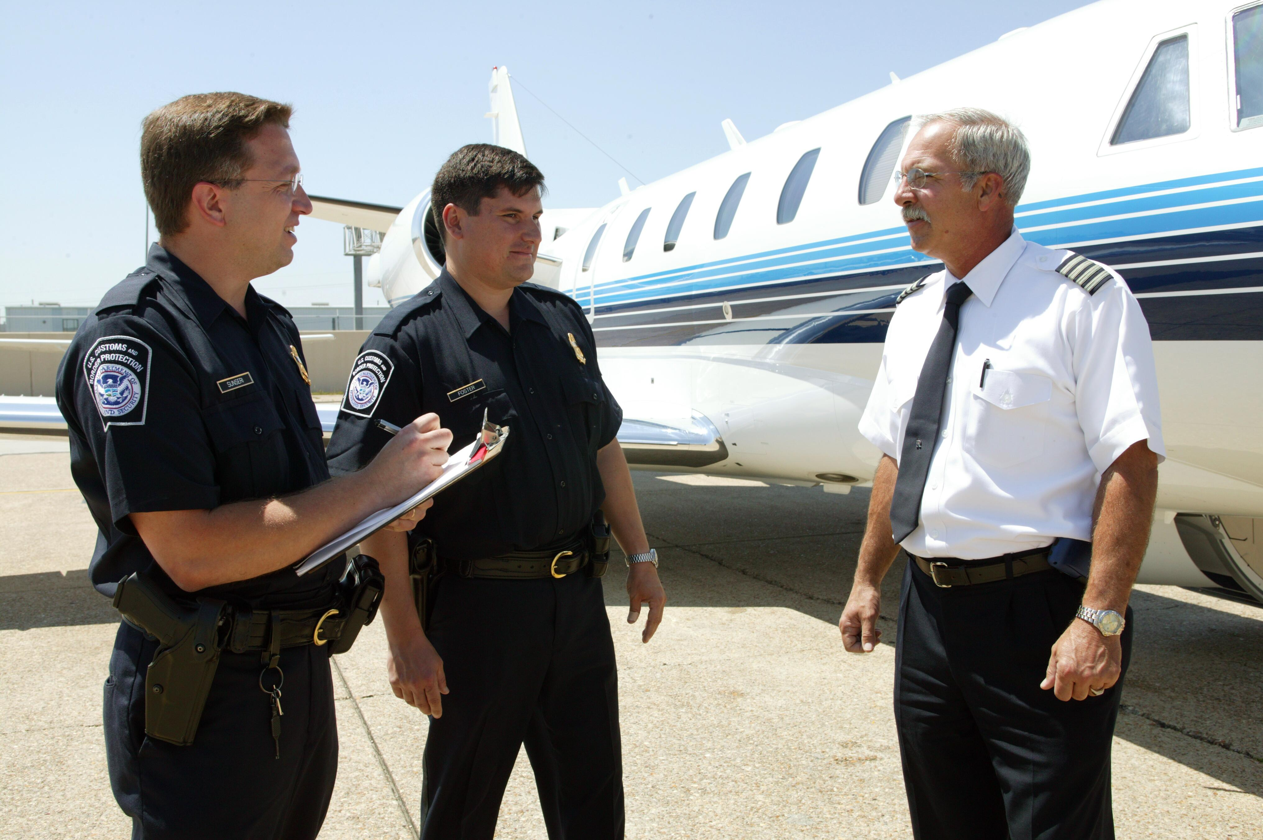 CBP Officers conduct a routine interview with the pilot of a small commercial aircraft after a flight.