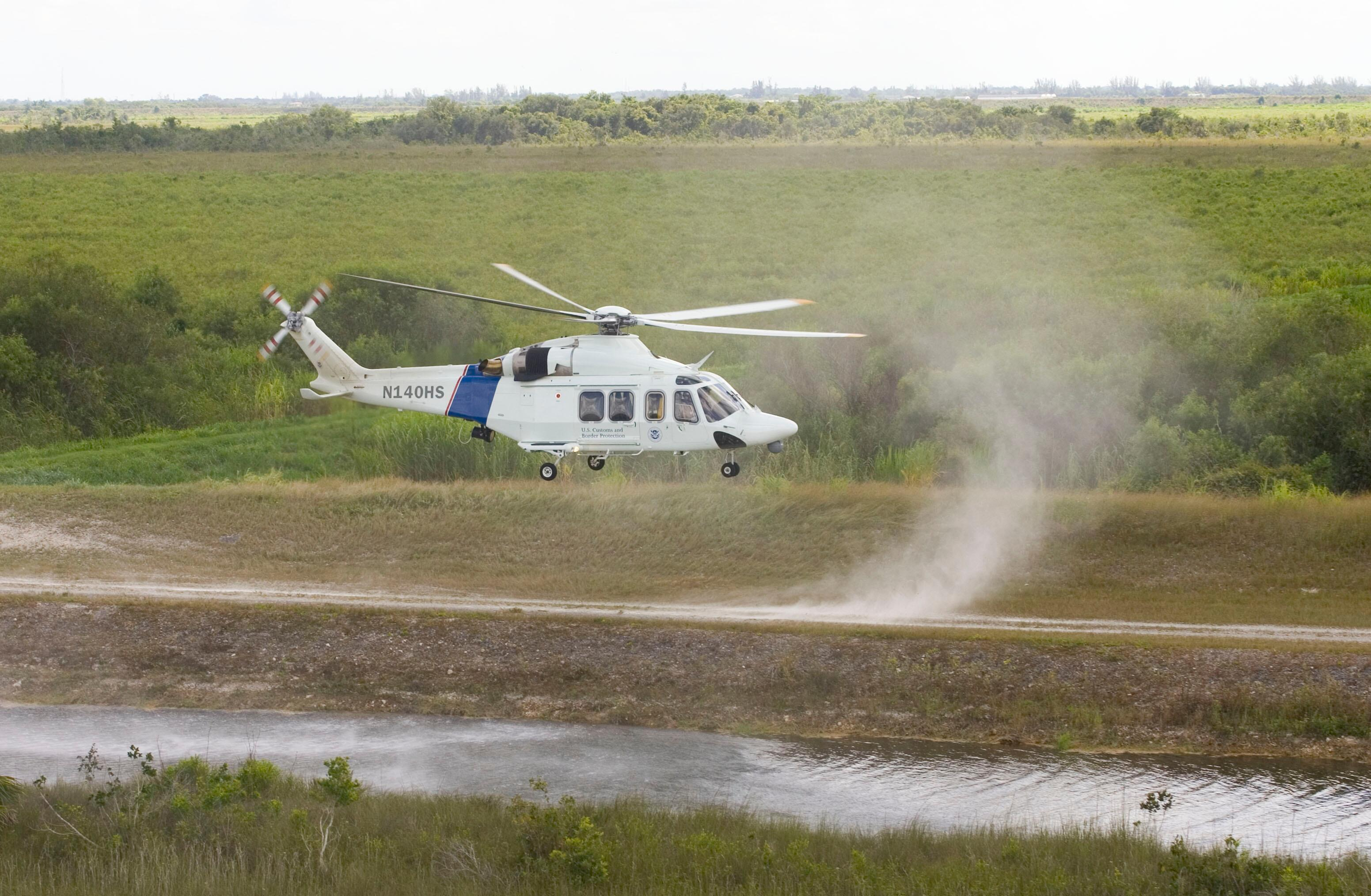 A CBP AW-139 helicopter lands in a remote area.