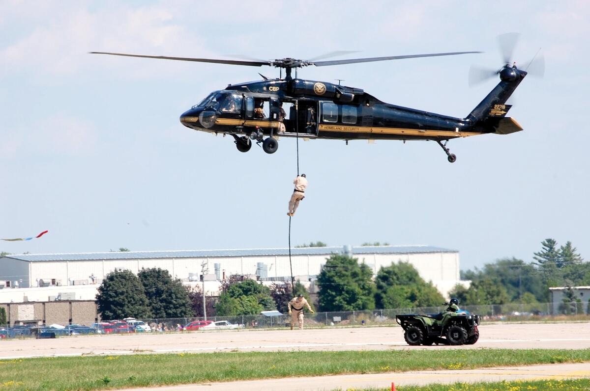 UH-60 Black Hawk helicopter with tactical agents demonstrating fast-rope techniques.