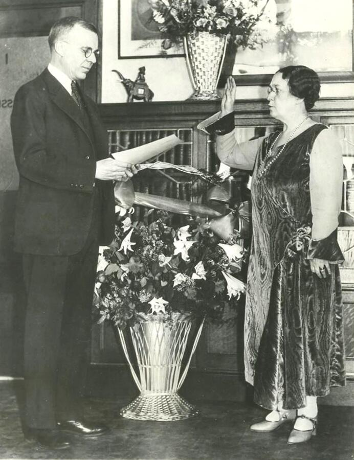 Anna C. M. Tillinghast is sworn-in for her second four year term as district commissioner of immigration for the port of Boston in February 1931. Judge Harold Williams administers the oath. In 1933, Tillinghast was removed from office after two years into her second appointment because Democrat Franklin D. Roosevelt had been elected president.