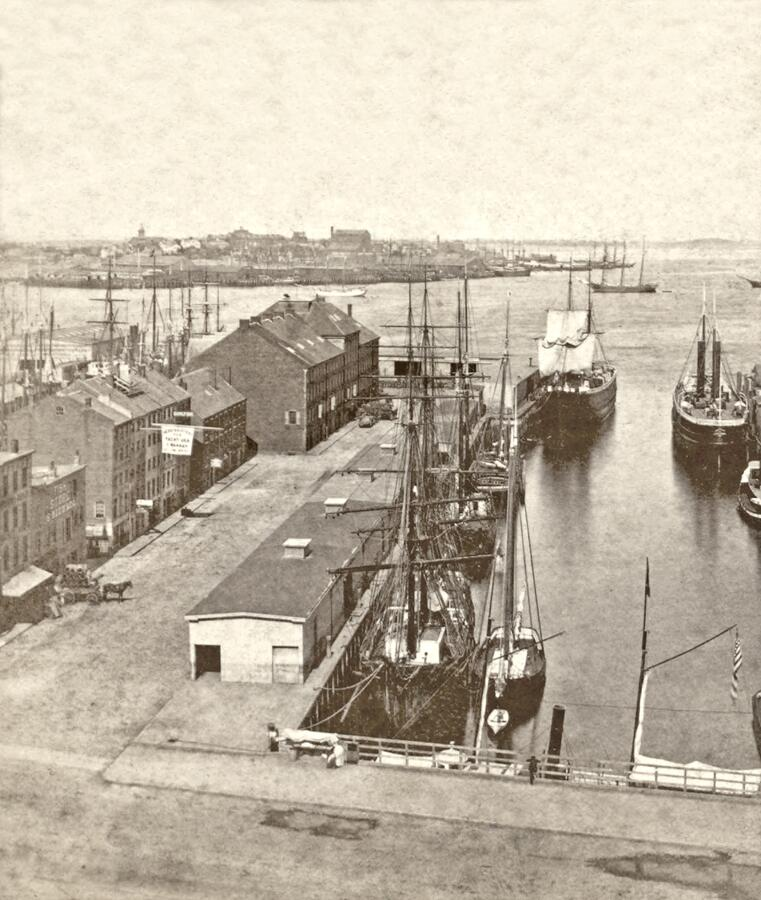 19th century stereoscopic view of Long Wharf in Boston Harbor. The large stone building last on the left is the Custom House Block, which still stands today. At the very end of the wharf, there is a single storey freight shed, similar to the sheds in the foreground. An immigrant station was constructed on top of this of this shed (see next photo) that would serve as the Boston immigrant station until 1920