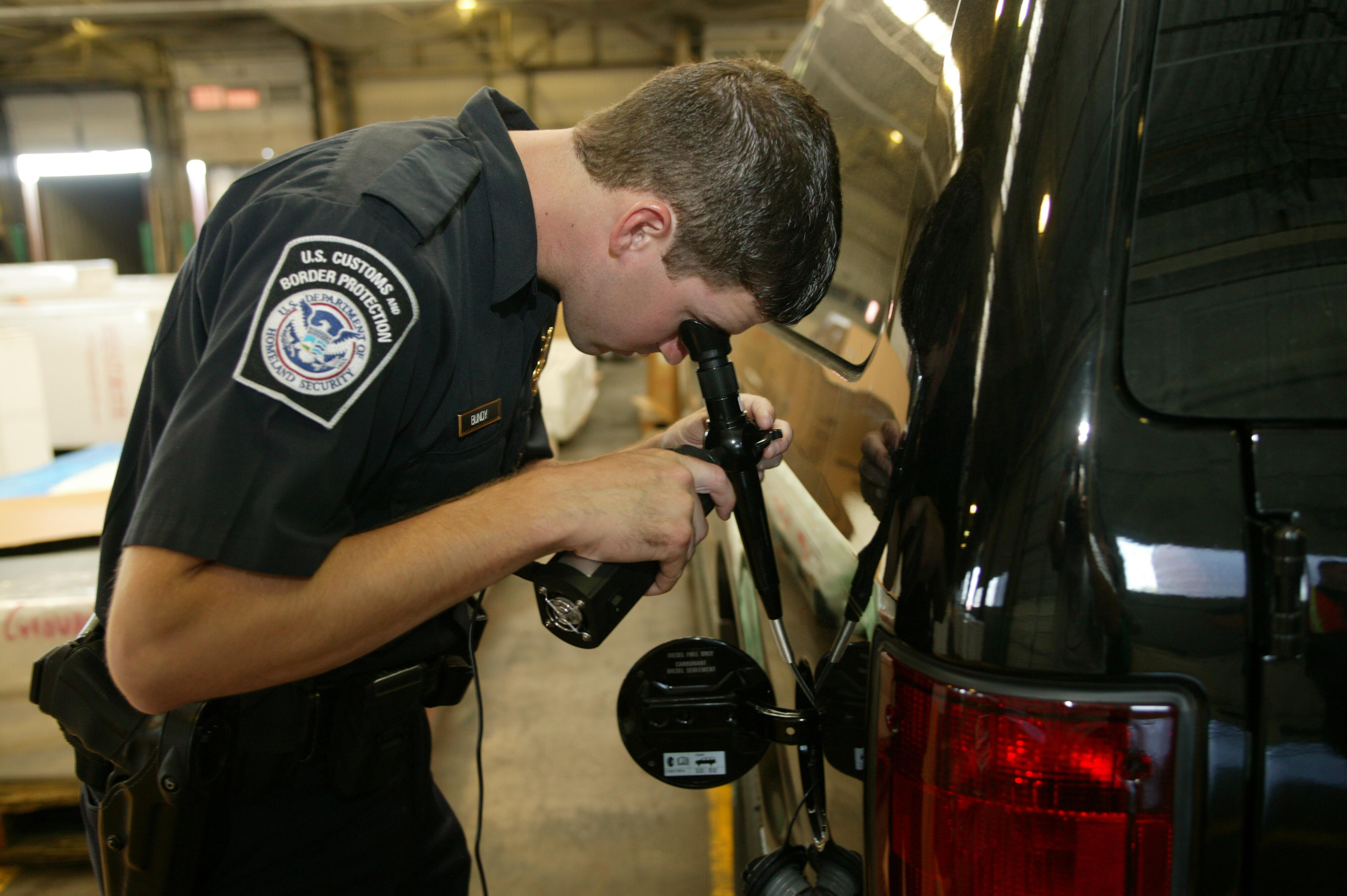 "This CBP officer uses a high tech device to ""peek"" inside a drum for contraband."