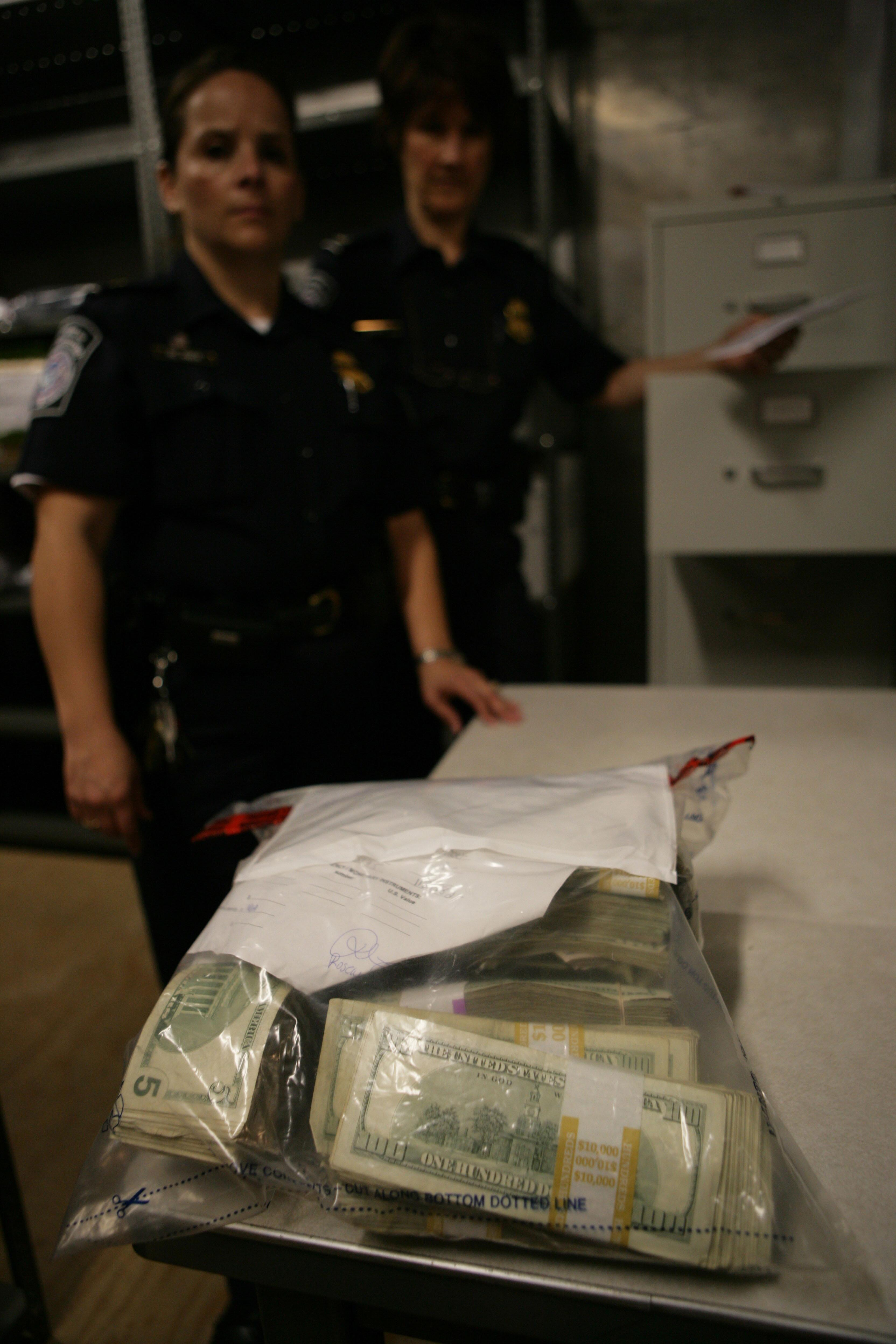 A CBP Officer displays a large bag of seized currency.